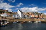 Boats moored at stone pier in Crail Harbour with Crail House lookout turret over the North Sea in Fife Scotland UK