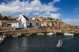 Fisherman on boat leaving Crail Harbour with stone piers and Crail House turret overlooking the North Sea Scotland UK