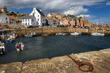 Fisherman on boat returning to Crail Harbour with stone piers and iron morring ring on the North Sea Scotland UK