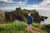 Scottish female tourist visitor at top of cliff above Old Hall Bay with Donnottar Castle ruins on the North Sea Scotland UK