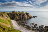 Pebble beach at Old Hall Bay North Sea with Donnottar Castle Medieval clifftop fortress ruins near Stonehaven Scotland UK