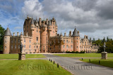 Front lawn of Glamis Castle childhood home of Queen Mother with statues of King James I and Charles I with sun and clouds Scotla