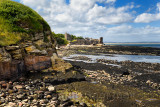 St Andrews Castle ruins with wall to rocky ocean with tide pools and Castle Sands beach in St Andrews Fife Scotland UK