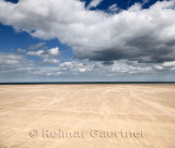 Blowing sand in High wind on wide St Andrews West Sands beach with blue sky and white clouds and North Sea at St Andrews Fife Sc