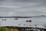 Three boats at low tide on Holy Island of Lindisfarne with Bamburgh Castle and Farne Islands on the North Sea England UK