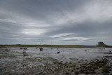 The Ouse with anchored boats at low tide from Willy Pots Rock on Holy Island with Lindesfarne Castle under renovation England UK