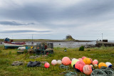 Bright fishing bouys and lobster pots on shore at The Ouse bay on Holy Island with Lindisfarne Castle under renovation England U