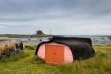 Bright door of shed made of overturned boat cut in half on Holy Island with Lindisfarner Castle ruins under renovation England U