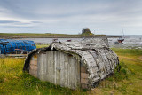 Weathered hull of shed made of overturned boat cut in half on Holy Island with Lindisfarner Castle ruins under renovation Englan