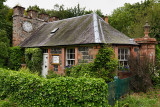 West Clock Lodge coach house in Sheriffmoor Plantation Forest at Eagle Lodge Scottish Borders Scotland UK with ivy and clock on
