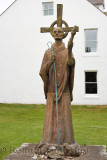 Statue of St Aidan first bishop of Lindisfarne monastery with white Manor House Hotel on Holy Island at the Priory ruins England