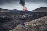 """Despite this being an otherworldly experience, it begins, like many adventures, in a car park. Ever since the Gerlingadalur eruption began on March 19, 2021, Icelanders—and now vaccinated international visitors such as myself —have made pilgrimages to see the lava spew, bubble, and flow across this stretch of the Reykjanes Peninsula in southwestern-most Iceland. What's astonishing is that this once-in-800-years display of nature's force is only a 45-minute drive south of Reykjavík. It's even closer to Keflavík Airport, the largest airport in the country—a mere 20 minutes by car. Imagine that: an active volcano one would deem """"accessible."""" You could land in Iceland in the morning from the United States (there are flights from Boston, JFK-NYC, and Washington, D.C., as of May), await your negative COVID test results at a nearby hotel, and once cleared, see the volcano erupt in the same day."""