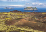 The view of the islands of Elliðaey and Bjarnarey from the extreme side of the new land created by the 1973 eruption on the island of Heimaey, Vestmannaeyjar (the Westman Islands), Iceland. In the distance is visible, on Iceland mainland, Eyjafjallajökull, the Glacier of the Islands, that takes its name from the Vestmannaeyjar. at Bjarnarey there is a lodge ,while at Elliðaey (left ) there is a mystery of one of the world's loneliest house on remote island that has been empty for over 100 years