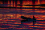 2018 October 22 Canoe in silhouette on water reflecting purple and yellow from the sky before sunrise.