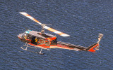 Search and Rescue Helicopter flies over the reservoir in the Hetch Hetchy Valley of Yosemite NP