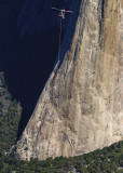 Helicopter transporting a team member as seen from Taft Point with the foot of El Capitan below in Yosemite National Park