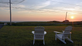 A pair of Adirondack chairs and a sunset