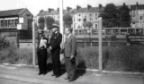 UNDATED - REG FISK, WITH A COMMANDER AND PADRE AT KENISINGTON (OLYMPIA) STATION.jpg