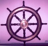 UNDATED - DICKIE DOYLE, WHEEL FROM HMS GANGES II, IN THE OFFICE OF MIDLAND IRON AND STEEL, NETHERTON.jpg