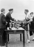 1945, JULY - CDR. WGF SMITHWICK, PRESENTING A BOXING TROPHY AT RNAS HENSTRIDGE, SEE NOTE BELOW.jpg