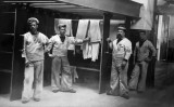 1914c - 4 POSSIBLE INSTRUCTORS BESIDE THE DRYERS IN THE LAUNDRY.jpg