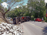 A 10-wheeler truck carrying GI pipes lies on its side after overturning in a winding portion of the Rosario-Pugo Road which leads to Marcos Highway. The accident, which happened shortly before 11:00 am of May 17, 2019, blocked the entire width of the road, rendering this route to Baguio City impassable to all motor vehicles. The unidentified driver was injured in the accident and rushed by good Samaritans to the nearest hospital. The truck, with license plate number RGA-687, is owned by DMAR Trucking Services in Baguio City. It is estimated that the road will remain impassable for many hours because a large crane is needed to lift and move the truck aside.  Photo by Romy Ocon, Email -  romy.ocon@yahoo.com
