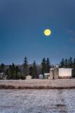 Full moon setting behind a farmstead 1