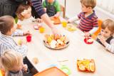 Preschool-Teacher-With-Class-Lunch-Time-Lessons.jpg
