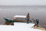 Taxi driver Robert Blueboy waits by his boat on the Moose River.