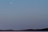Pale moon in the Christmas Day sky over the Moose River at Moosonee
