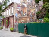 Judy next to a mural on the side of a house on Rue du Petit-Champlain in the Lower Town section of Old Québec.