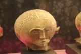 Anthropomorphic burial jar of unpainted head with perforations and partition at the center.