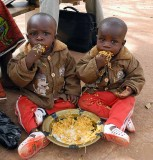 Little twins sharing their lunch in Burkina Faso