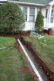 You dig trenches, lay pipe out to the street and connect the downspouts to the pipes.