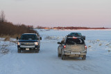 Vehicles driving along shore on way between Moosonee and Moose Factory