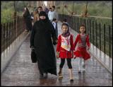 Walking grandmother over suspension bridge at Deir ez-Zor