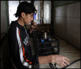 Young boy cooking coffe on a burner