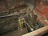 A corner of the basement, with stepladder holding up the electrical conduit7824