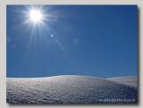 Sunrays over a snowy hill