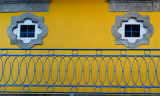 Twin windows, yellow wall, blue veranda
