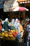 Muslim women walking by a fruit stand in the medina of Fès.