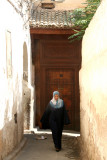 A Muslim woman walking in front of an ancient door in the medina in Fès.