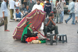 Exotic-looking Moroccan woman sitting in front of a colorful umbrella at Place Djemaa El-Fna.