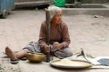 Lady pounding rice, Nepal.
