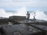 274 - Daniel and Alex running away as a big wave splashes on the concrete blocks