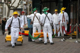 dressed in traditional white garb, cheese porters carry the cheese away in barrows after it has been weighed