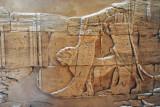 The god Apedemak walking a lion by a leash