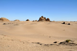 Ruins of the ancient pyramids at Nuri rising out of a sandy desert