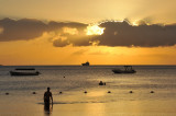 A bather wades in the shallow water at sunset, Mauritius