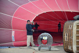 Ground crew members inspect the inside of the balloon as it is inflated with cold air